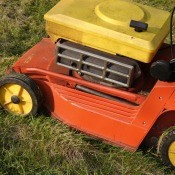 An old lawn mower, painted yellow and orange.