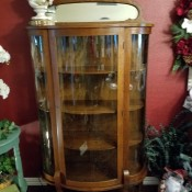 Value of a Curio Cabinet - a perhaps antique curio cabinet with curved glass front and sides and an oval mirror on top