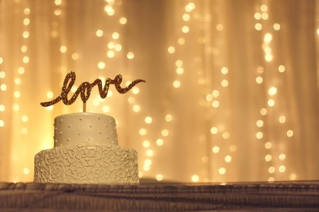 "White cake with a ""love"" topper, twinkling light backdrop."