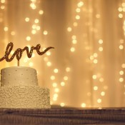 """White cake with a """"love"""" topper, twinkling light backdrop."""