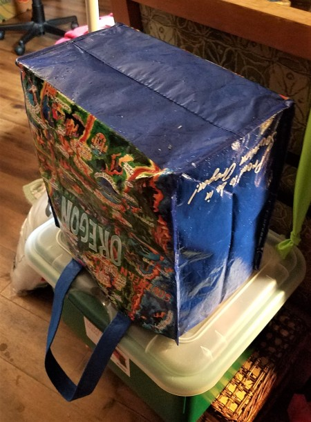 A shopping bag upended on a container to dry.