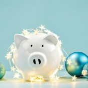 A piggy bank with Christmas lights and ornaments.