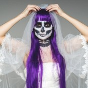 Halloween bride with purple hair and a painted face.