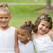 3 girls wearing a white dresses.