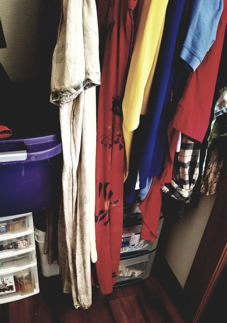 Clothing hung inside out in a closet, as a reminder that it needs to be mended.