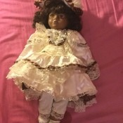 Identifying a Porcelain Doll - dark skinned doll wearing a lacy dress and hat