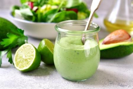 A small jar of green avocado mayonnaise.
