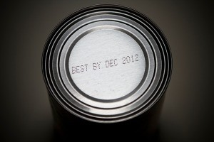 An expiration date stamped on the top of a food can.