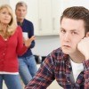 A young man looking irritated with his parents, who are also frustrated.