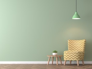 A green wall with a yellow striped chair in front of it.