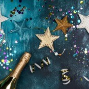 A blue background with stars, ribbons and a bottle of champagne.