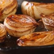 Baked onion halves on a sheet pan.