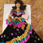 Value of a Franklin Heirloom Doll - dark haired doll wearing a long black dress with pink, teal, and gold ruffles and sequins