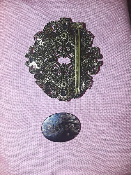 A metal brooch with the stone removed.