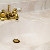 A cultured marble sink with gold fixtures.