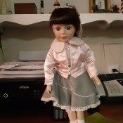 Identifying a Porcelain Doll - doll in pink jacket and gray skirt