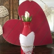 Transform any Vase into a One with a Valentine's Theme - red bottle with heart decoration with a rose bud,  in front of a red wood/paper heart