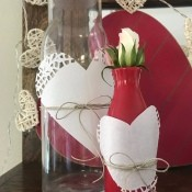 Transform any Vase into a One with a Valentine's Theme - clear bottle and red vase decorated with paper doily hearts