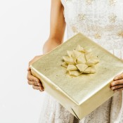 Golden wedding gift in the hands of a woman wearing a white dress.