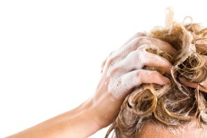 A person washing their blonde hair.