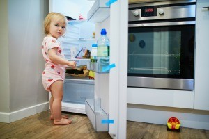 A toddler in an open refrigerator.