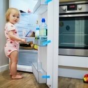 A toddler in an open refrigerator.