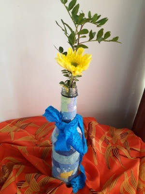 Fabric Covered Specimen or Bud Vase - greenery and a yellow flower in bottle with a blue ribbon tied to neck