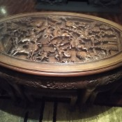 An intricately carved round wooden table.