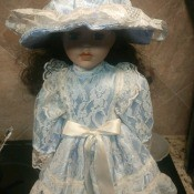 Identifying a Porcelain Doll - doll wearing a blue dress and hat covered in white lace