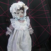 Identifying a Porcelain Doll - doll wearing an eyelet trimmed bonnet and pinafore over a pink dress