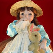 Identifying a Porcelain Doll - doll with a hanky to her nose, wearing a straw hat and blue satin dress with eyelet bodice and skirt, holding a stuffed bunny