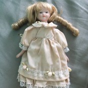 Identifying a Porcelain Doll - small doll wearing a light peach colored dress