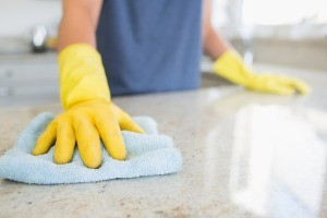 A person in gloves cleaning a kitchen counter.
