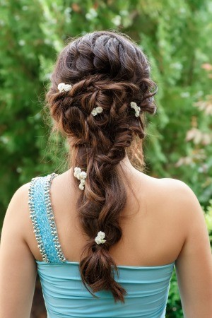A brunette bridesmaid with a decorative hairstyle.
