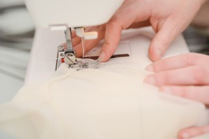 A wedding dress being sewn on a sewing machine.
