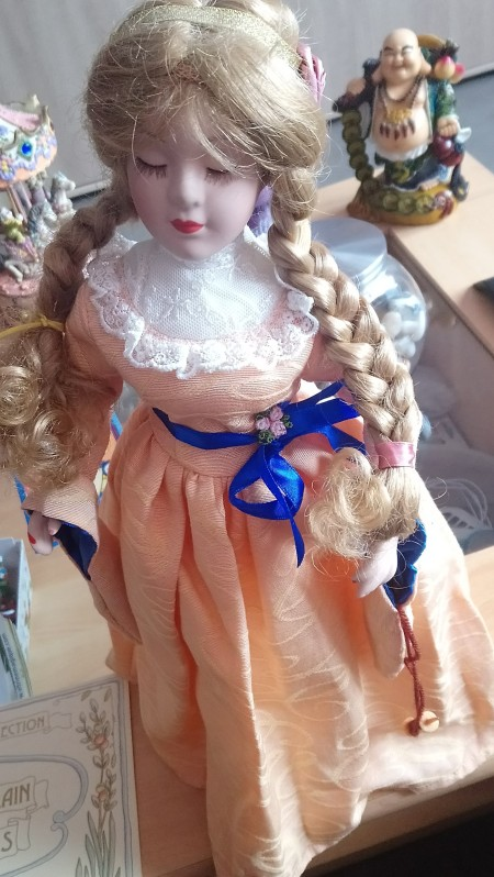Value of a Porcelain Doll - doll in peach colored dress with blond braids