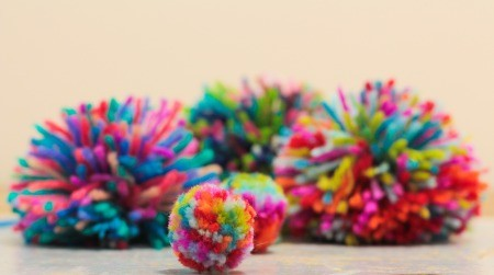 A collection of brightly colored pom poms.