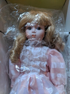 Value of a Seymour Mann Doll - doll wearing a pink dress with white lace and ribbon on bodice and sleeves, wrapped in plastic
