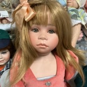 Identifying a Porcelain Doll - doll with peach colored bow in her hair
