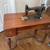 Value of a Vintage White Sewing Machine and Cabinet - black and brass vintage machine in a lovely wood cabinet