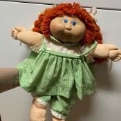 Value of a Cabbage Patch Doll - red haired doll wearing a green and white gingham dress