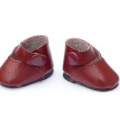 A pair of red doll shoes.