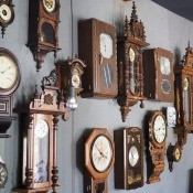 A wall of antique clocks.