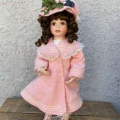 Value of an Ashton Drake Galleries Doll - doll wearing a light pink long coat with matching hat and shoes