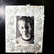 painted puzzle piece photo frame with a young boy's photo inside