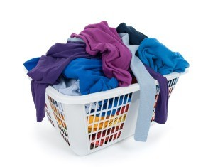 A white laundry basket full of clothing.