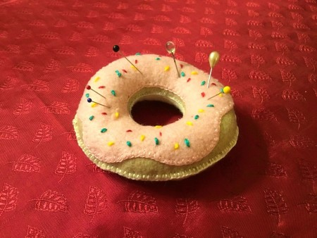 tan felt donut shaped pin cushion with pink felt frosting