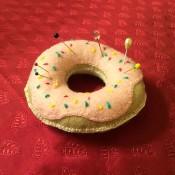 tan felt donut shaped pin cushion with pink felt frosting