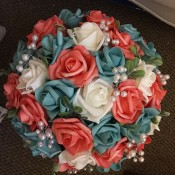 A wedding bouquet with teal and pink roses.