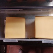 Sliced cheese in a plastic container.